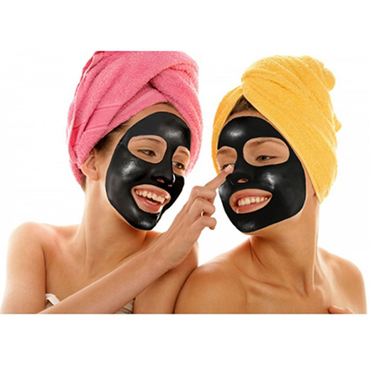 Två kvinnor som använder rengörande svart ansiktsmask.