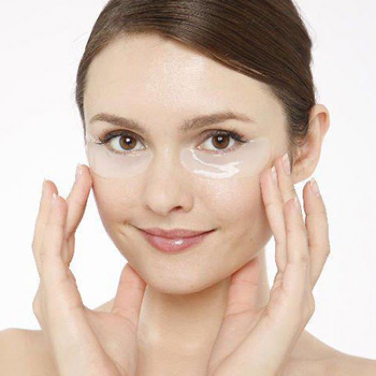 Kvinna som använder ögonplåster för att minska mörka ringar under ögonen.