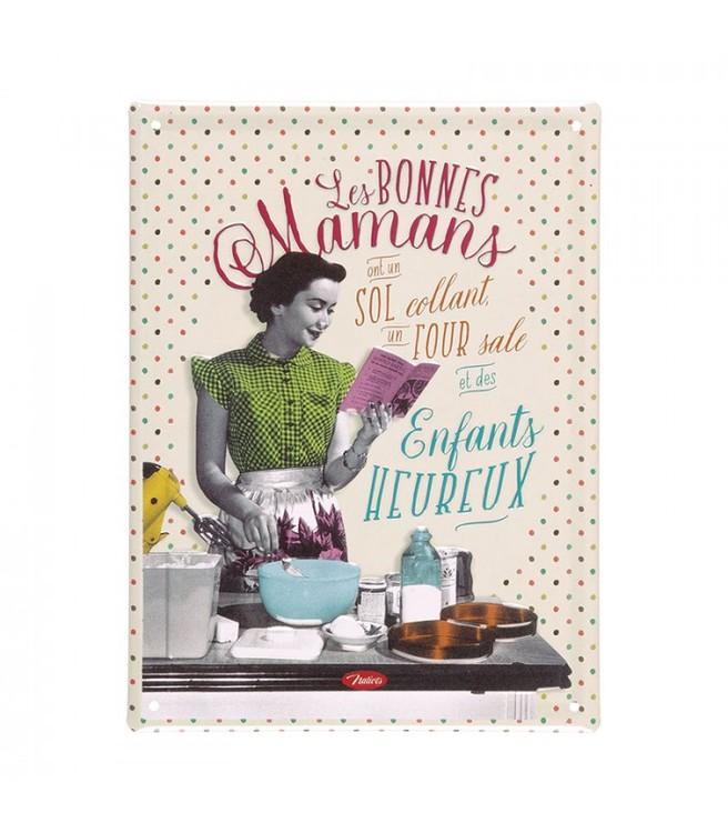Plåtskylt, en kvinna som lagar mat och tittar i en receptbok.
