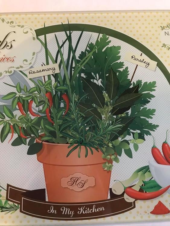 Persilja, chili och rosmarin i en kruka som motiv på skärbrädan i glas.