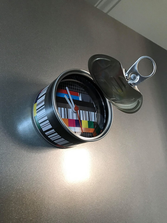 Klocka med magnet att sätta på kylskåpet i köket, en konservburk med flagga som motiv.