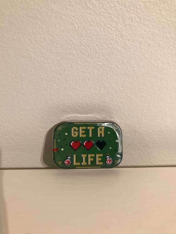 Grön liten ask i plåt för mintpastiller, get a life som motiv.