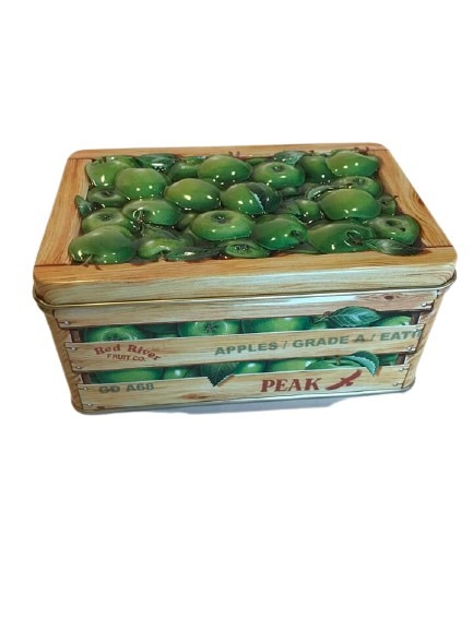 Liten plåtburk med gröna äpplen som motiv.