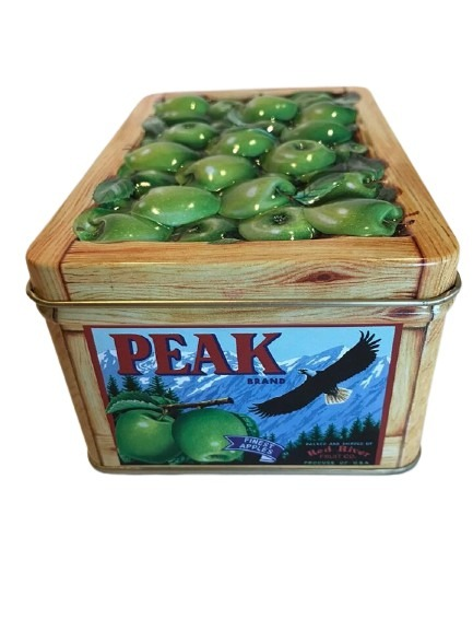 Fruktlåda i plåt med motiv av gröna äpplen.