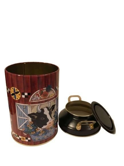 En plåtburk med två lock som är en mjölkkanna, motiv av kor i ladan hemma på gården.