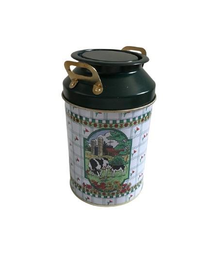 Svarta och bruna kor som motiv på denna lilla mjölkkanna, i plåt och med guldhandtag.