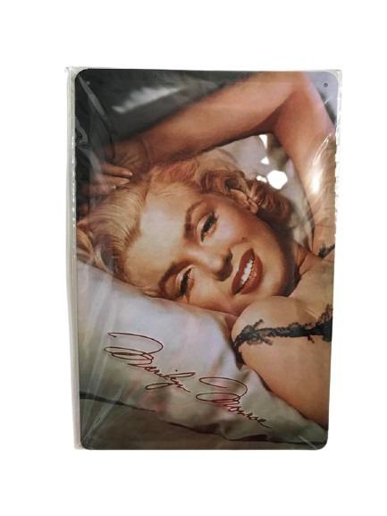 Marilyn Monroe på en plåtskylt med en sexig look liggandes i en säng.