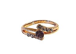 Guldfärgad ring med lila sten