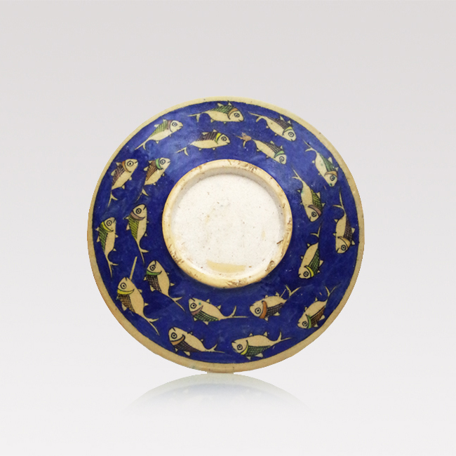 A large, round handmade Iranian serving plate with hand painted colourful fish pattern on blue.