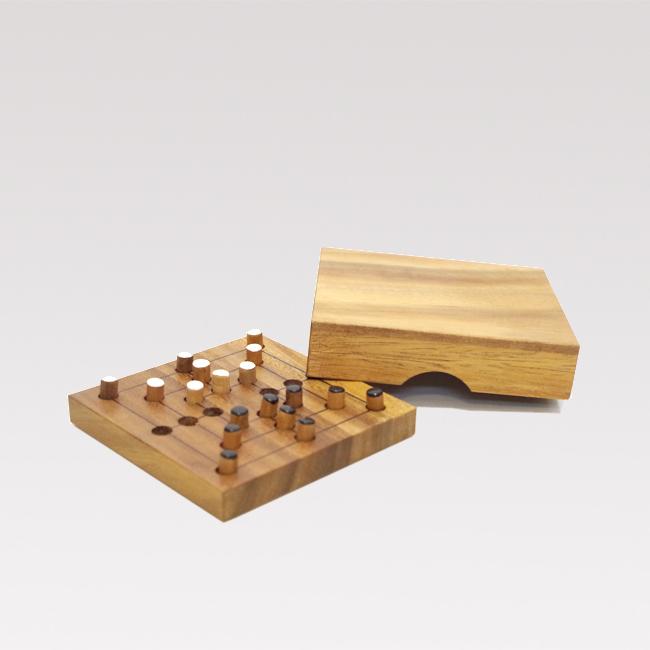 Litet handgjort brädspel i teakträ. Fyrkantigt 11x11 cm med spelpjäser i svart och vitt trä och lock.