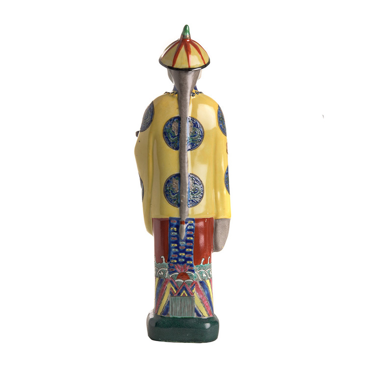 Handmålad kinesisk porslinsfigur med gul jacka och hatt. Baksida med lång hästsvans och vackert detaljerad målning av kläder.