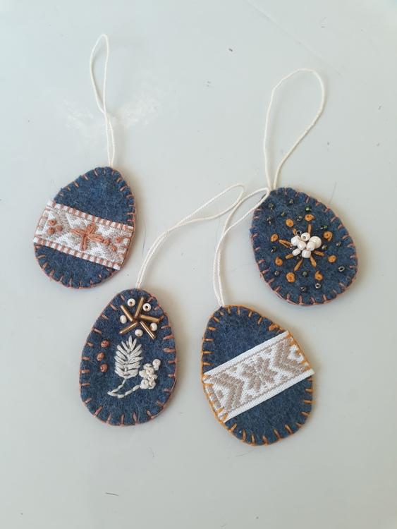 Påskägg av ylletyg med dekorationer av band och pärlor