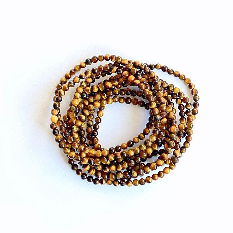 Elastiskt armband av små pärlor av Tigeröga