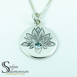 Hand-engraved lotus pendent in silver with a topaz