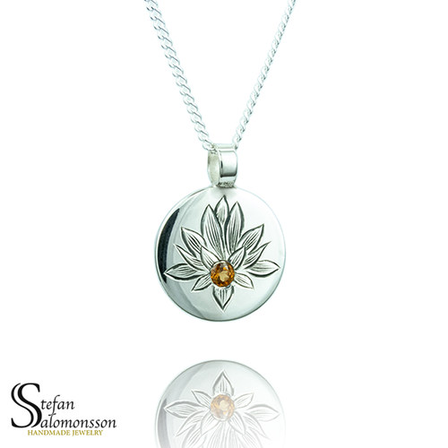 Hand-engraved lotus pendent in silver with a hessonite garnet