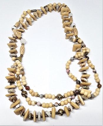 Flerradigt halsband med fina detaljer i sten, metall och ben