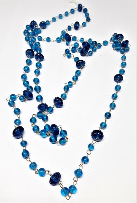 Långt halsband med kulor i olika ljusare blå toner