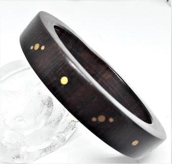 Stelt armband av trä med guldfärgat mönster
