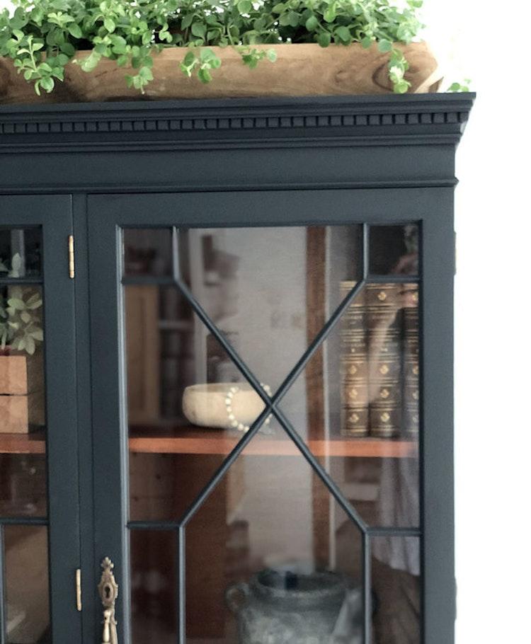 Stort svart vitrinskåp med många vackra detaljer