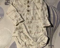 Vit body med farfarsknäppning och fågelmönster i beige och rött samt ett par vita byxor från Newbie stl 56