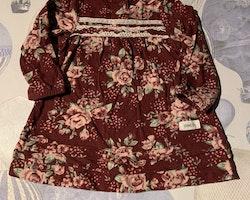 Vinröd klänning med vit spets och rosmönster samt en vit hålstickad kofta med hjärtdekorerade fickor från Newbie stl 62