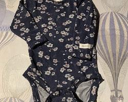 Mörkblå body med ljusgrå och rosa blommor samt ett par rosa byxor från Newbie stl 62