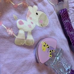 Ljuslila romper med girafftryck från Jacky stl 50 samt en matchande napphållare