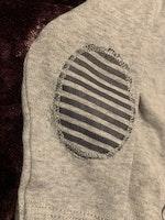 Ljusgrå body med texttryck och armbågslappar från Newbie stl 56