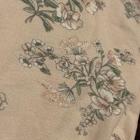 Ljusrosa body med volanger och blomster/fjärilsmönster från Newbie stl 56