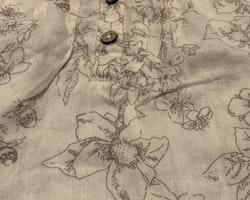Vit blus med spetskrage och  ljusbrunt mönster av blommor, fåglar mm från Newbie stl 56