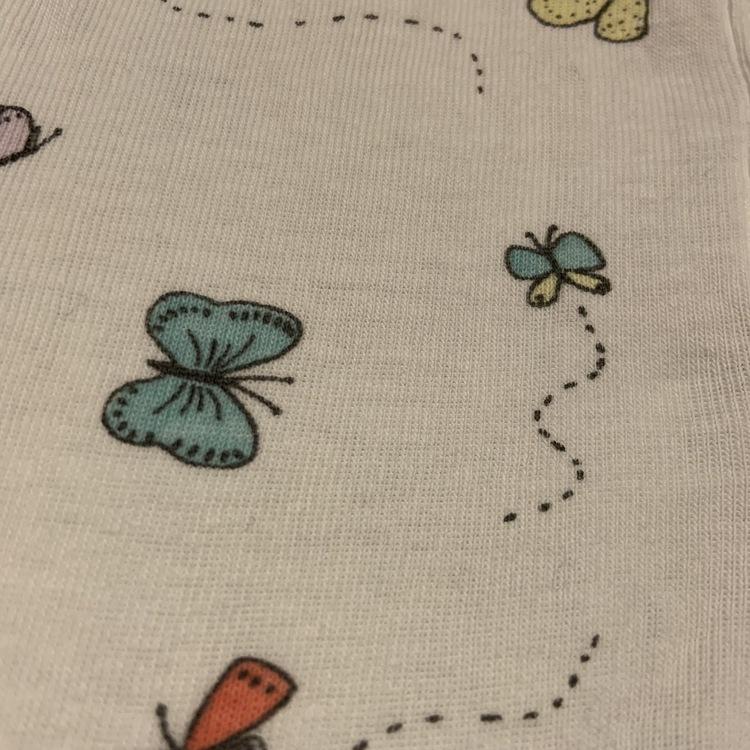 Ljusrosa omlottbody och vita byxor med fjärilstryck från Lindex stl 56