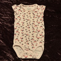 Ljusrosa kortärmad body med mönster av jordgubbar från Name It stl 62