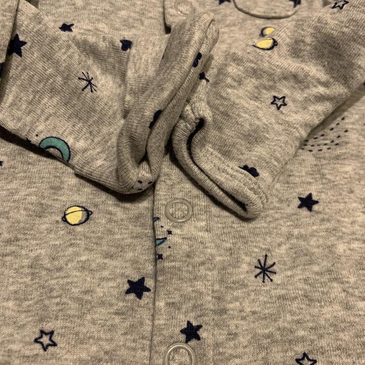 Set med grå pyjamas med rymdtemamönster samt matchande mössa, haklapp och strumpor från Carters str 62
