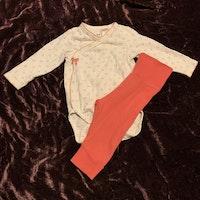 Set med vit omlott body med mönster i rosa och grönt samt rosa byxor från HM str 62