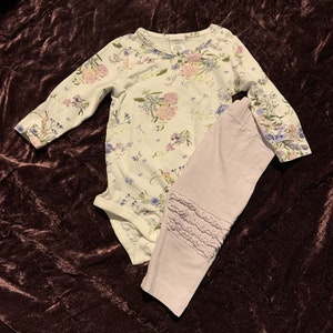 Set med vit body med blommönster i grönt, blått och lila samt lila byxor med volanger på knäna från Lindex str 62