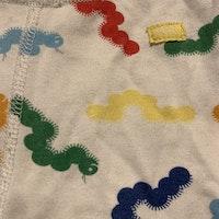 Vita byxor med mönster av färgglada larver från PoP stl 62