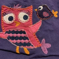 Lila body med mörkrosa kantband och fågel applikationer i rosa och lila från Lindex stl 62