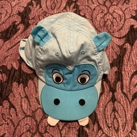 Blå keps med flodhäst applikationer och nedfällbart nackskydd från HM stl 62
