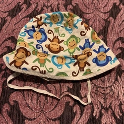 Solhatt med mönster av färgglada apor från Sytt och Smått stl 3-9 mån