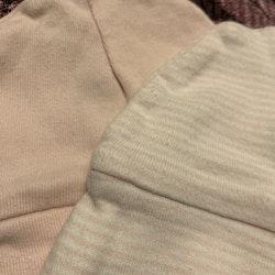 Två mössor i ljusrosa resp vit med ljusrosa ränder från Cubus stl 50/56