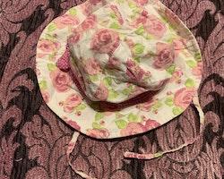 Blommig solhatt i vitt, grönt och rosa från Lindex stl 3-6 mån