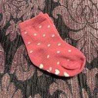 Ett par rosa strumpor med vita prickar och halkskydd stl 14-17
