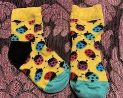 Ett par färgglada strumpor med nyckelpigor från Happy Socks stl 16-18
