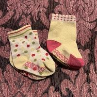 Två par strumpor i vitt, rosa, gult och grönt med halkskydd stl 16-18