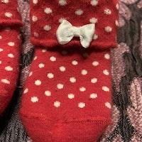Ett par röda strumpor med vita prickar och vit rosett från Disney Mimmi stl 10-12
