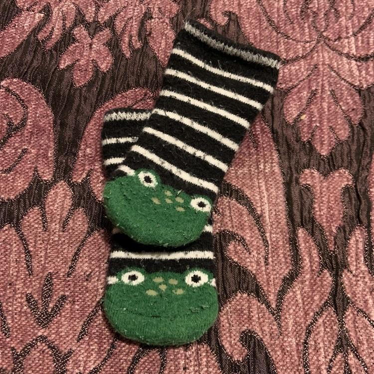 Ett par svart och vit randiga strumpor med en grön groda stl 10-11