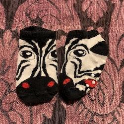 Ett par svartvita strumpor med halkskydd och zebra ansikte stl 13-15