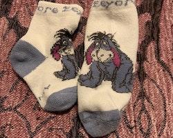 Ett par vita och blå strumpor från Disney med Ior stl 13-15