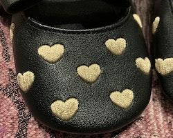 Inneskor i svart fuskskinn med broderade guldhjärtan stl 18-19
