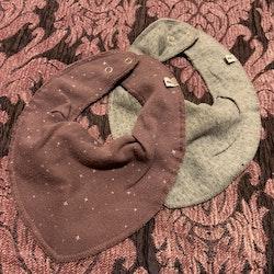 Två haklappar i lila och grått med mönster av bubblor och stjärnor från Pippi